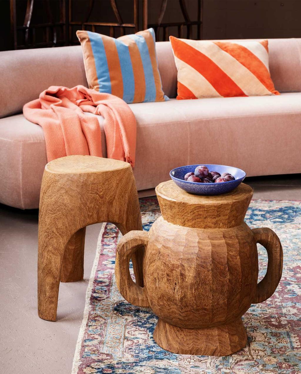 roze bank met gekleurde kussens en houten tafeltjes