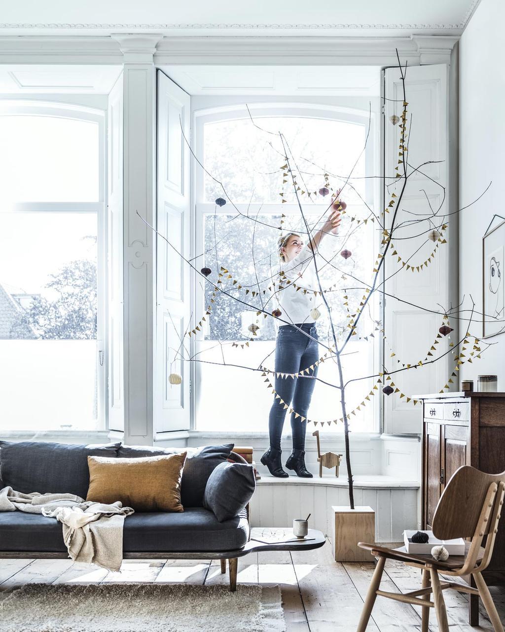 DIY een kerstboom van een mooie tak met slingers en papieren ballen uit de feest special.