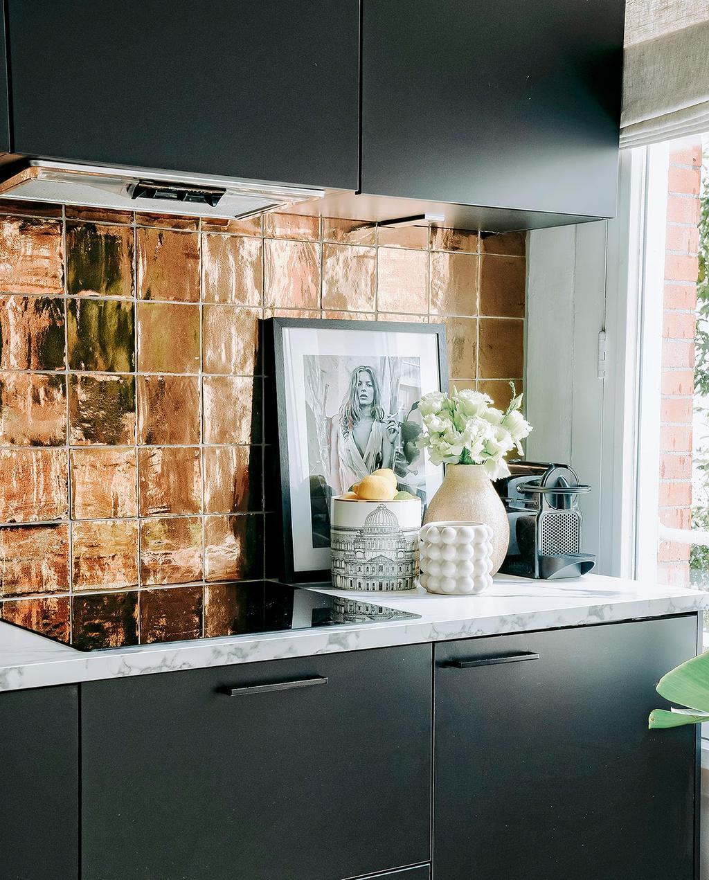 vtwonen 06-2021 | gouden interieur met gouden tegels in de zwarte keuken met een foto op het aanrecht I goud in het interieur