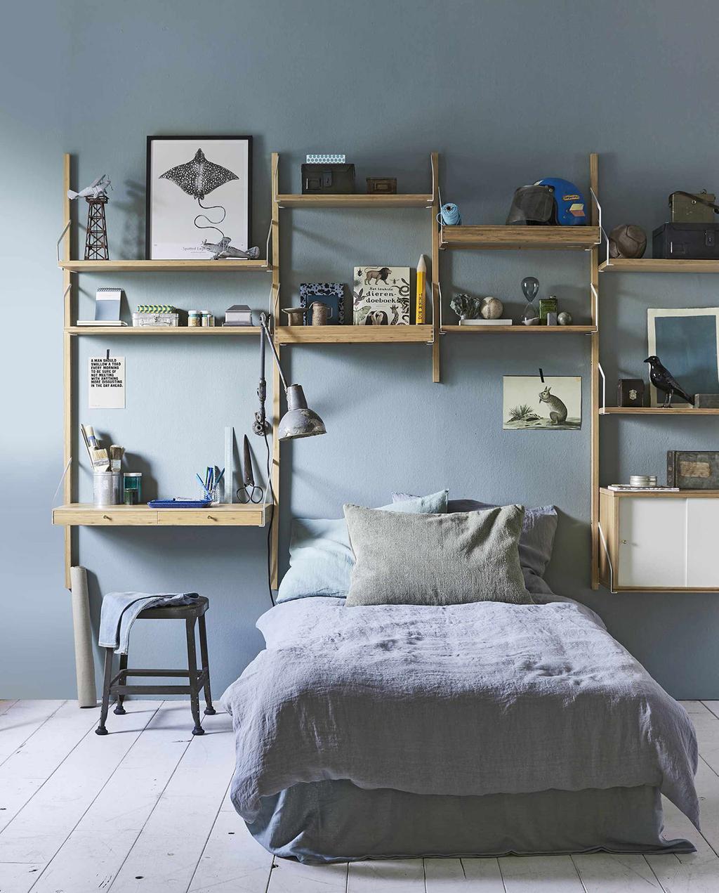 tienerkamer met houten kastwand, opgemaakt blauw bed, en bureau