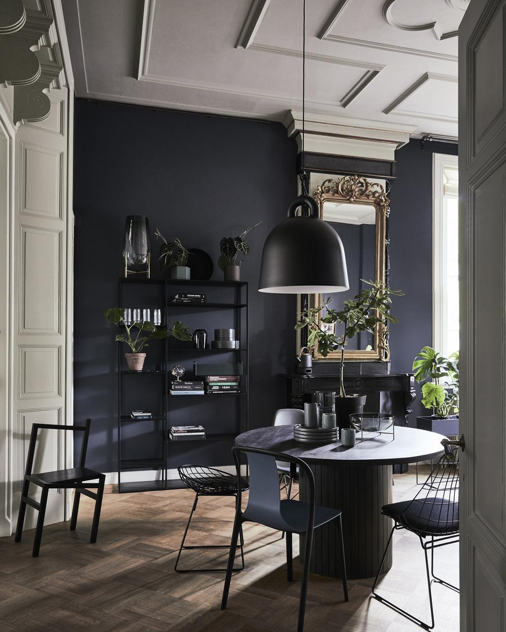 Woonstijl design interieur met donkerblauwe muur en vintage meubels