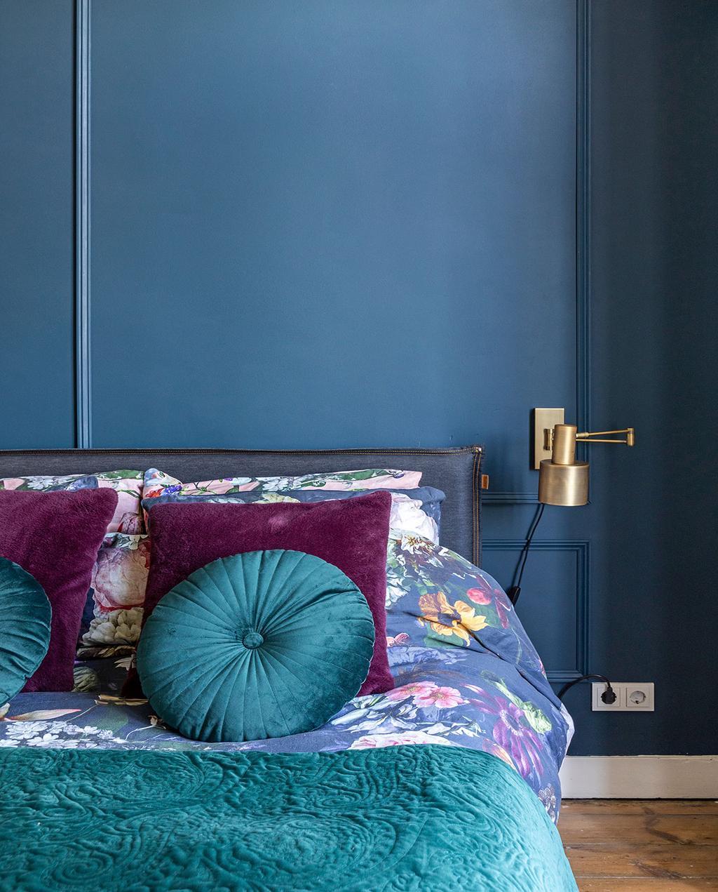 vtwonen 01-2021 | binnenkijken bij interior junkie blauw geverfde slaapkamer met opgemaakt bed, met paarse kussens