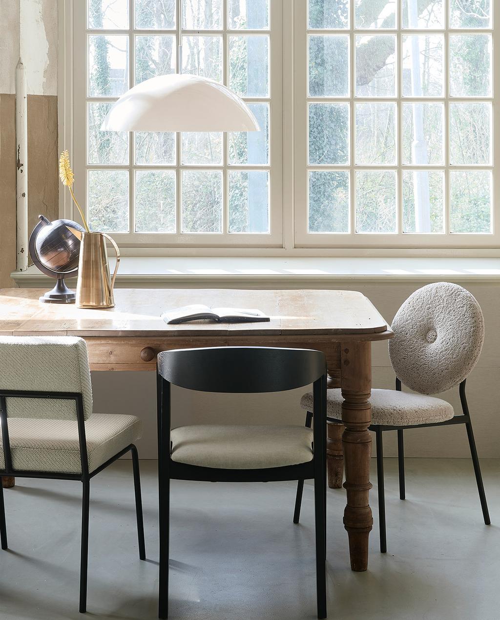 vtwonen 06-2021 | houten tafel met verschillende stoelen: een teddy stoel, zwarte eetkamerstoel en witte teddy stoel