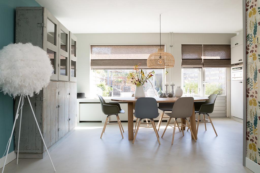Weer verliefd op je huis: ovalen eettafel met rotan hanglamp en stoere vitrinekast