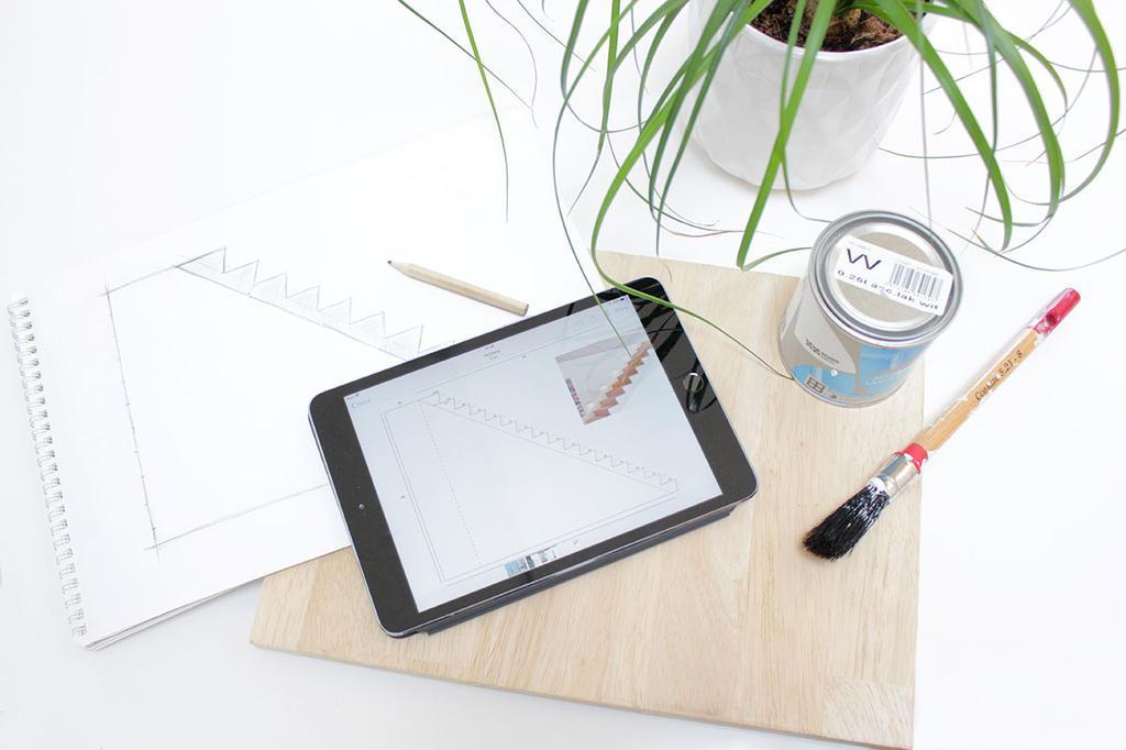 Tablet, plant en verfpot op tafel