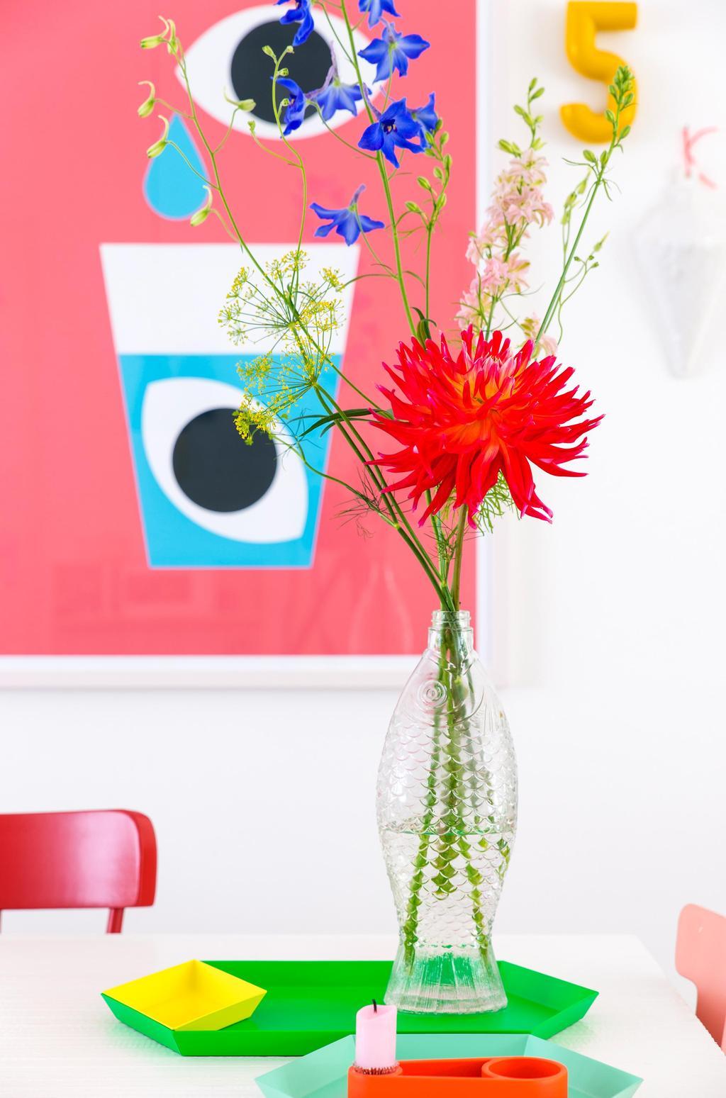 Glazen vissenfles met bloemen op tafel bij Oh Marie!