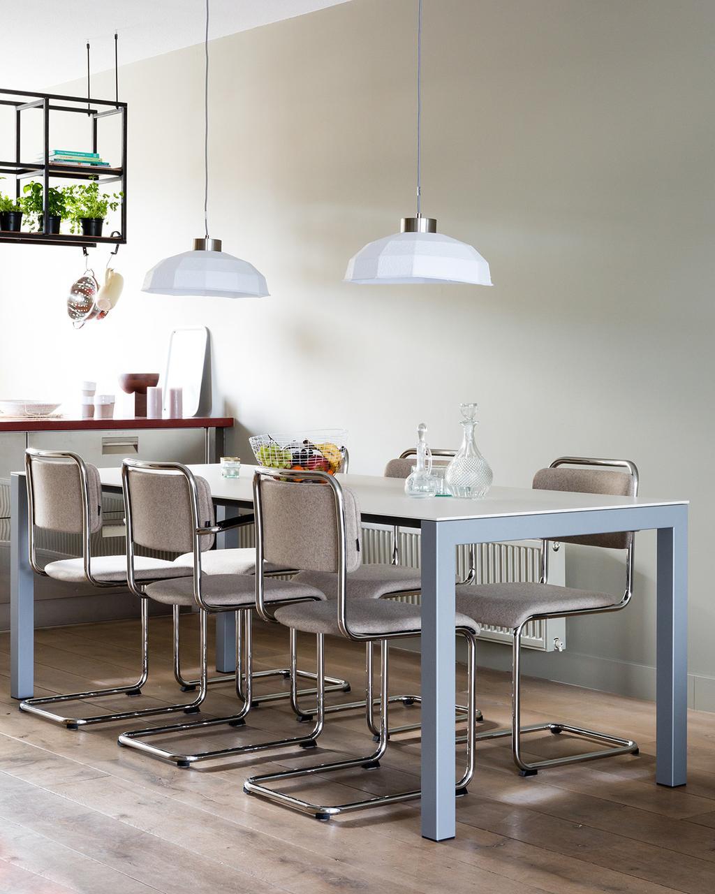 Eetkamer met witte hanglampen en grijze tafel