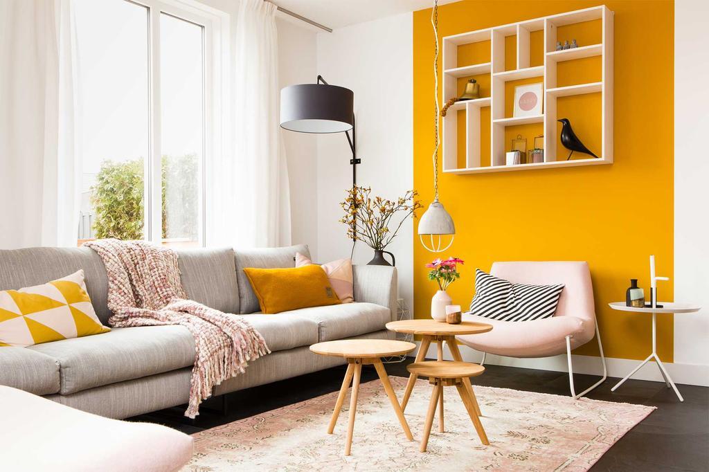 Grijze zetel voor een gele accentmuur in de woonkamer