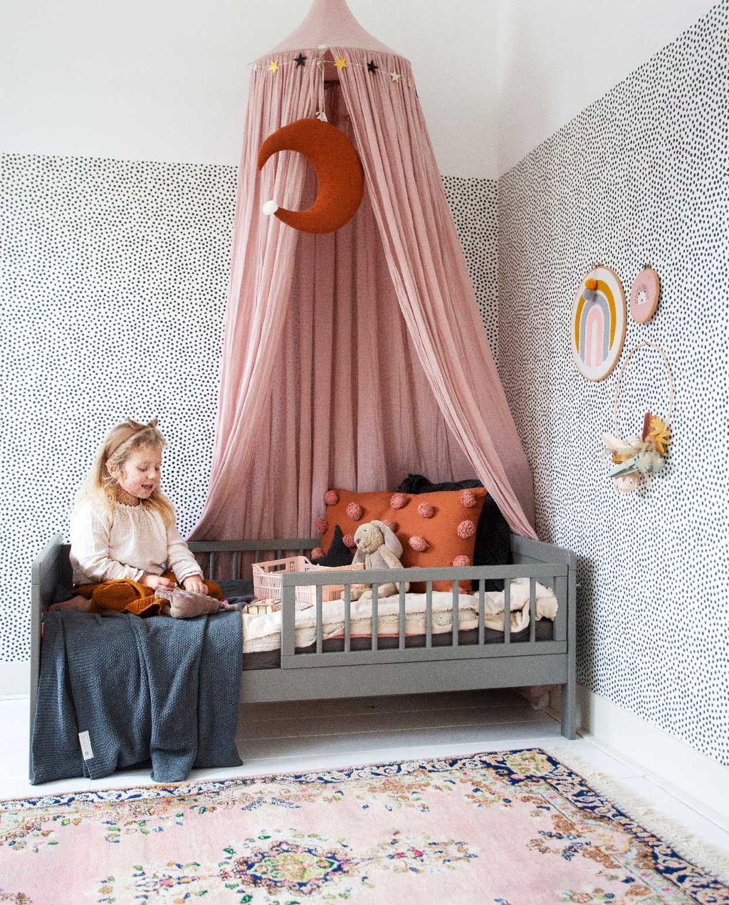 vtwonen 05-2020 | binnenkijken in een herenhuis in Amsterdam | kijkkamer kinderkamer grijs kinderbed met roze klamboe