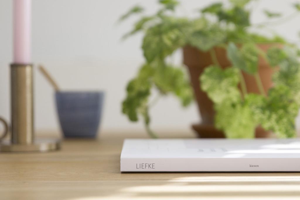 Liefke Magazine met op de achtergrond een kaars, plant en mok