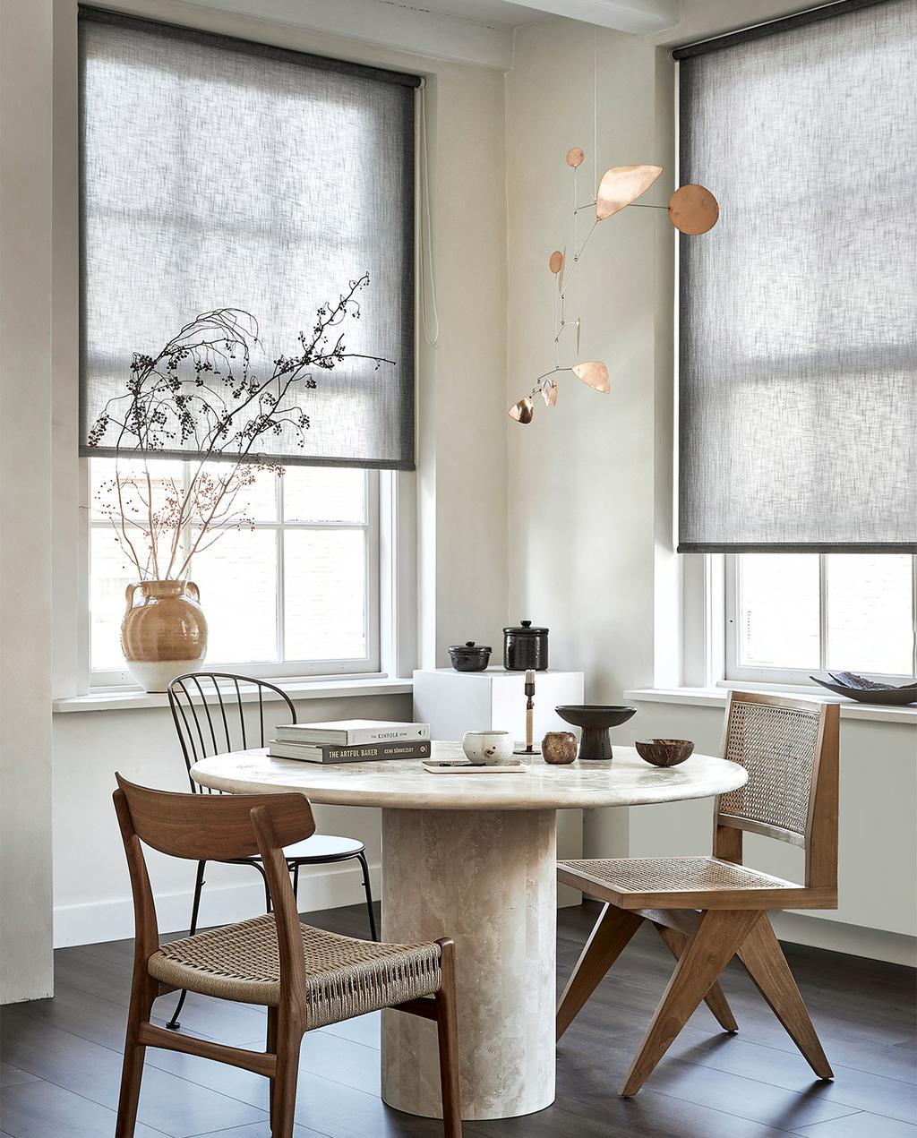 vtwonen 09-2021 | ronde eettafel met rotan stoelen in een beige interieur