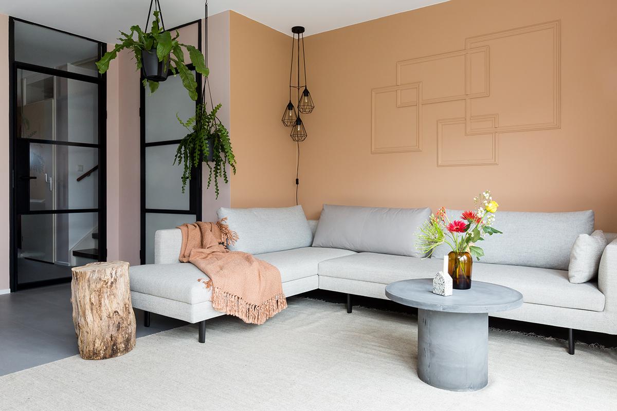 Woonkamer met een grijze hoekbank en grijze salontafel en glazen deuren met een staallook