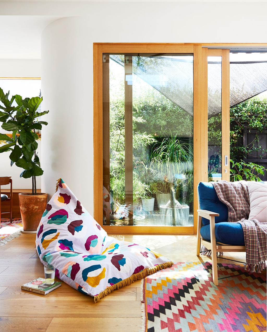 vtwonen binnenkijk special zomerhuizen 07-2021 | zitzak met stippen in de woonkamer, met openstaande tuindeuren en een gekleurd sisal vloerkleed