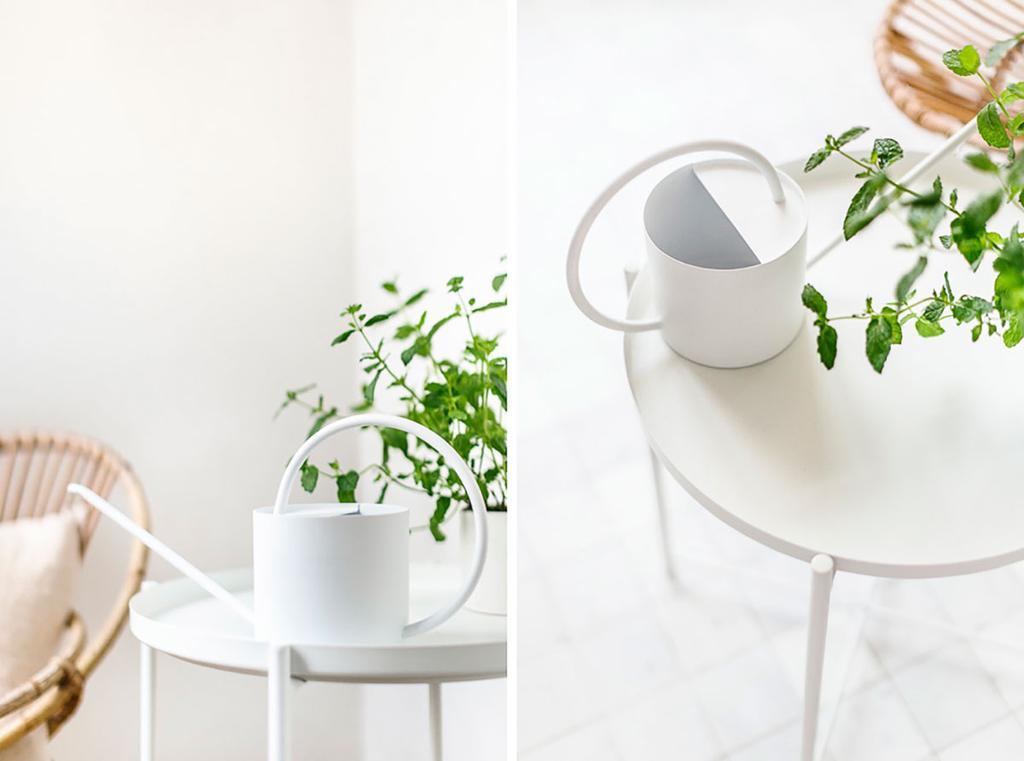 Een witte gieter staat op een wit tafeltje.
