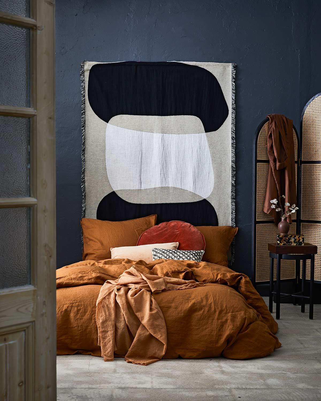 Blauwe slaapkamer met wandkleed boven het bed en een koperen dekbedovertrek
