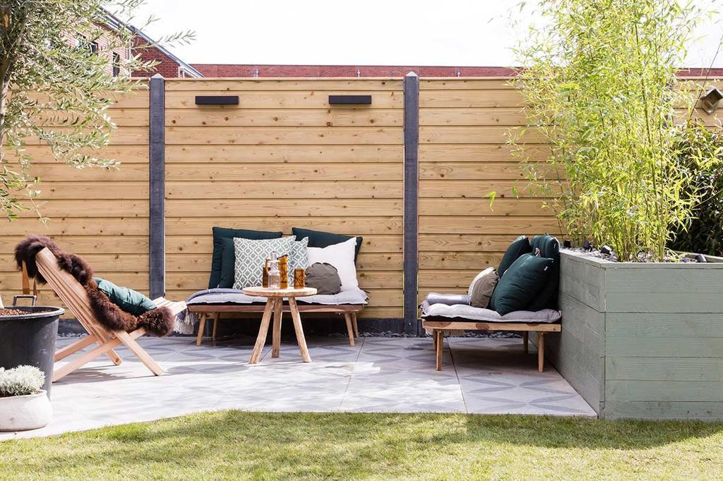 Loungehoek met vtwonen buitentegels en loungebankjes na een tuin make-over
