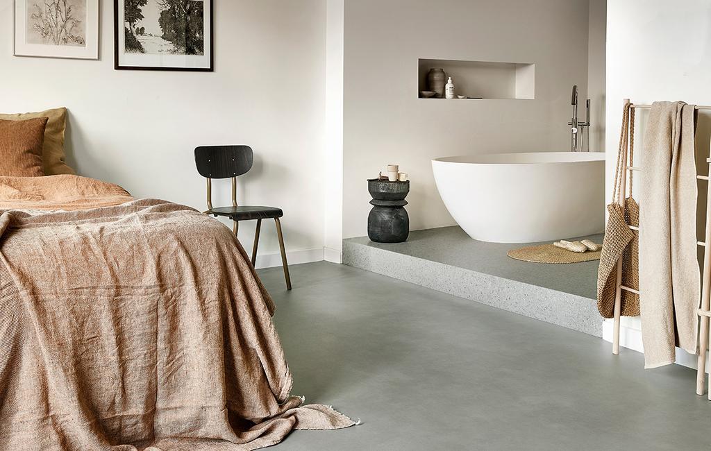 vtwonen 07-2021 | roze dekbedovertrek met een bad in de slaapkamer en een betonlookvloer