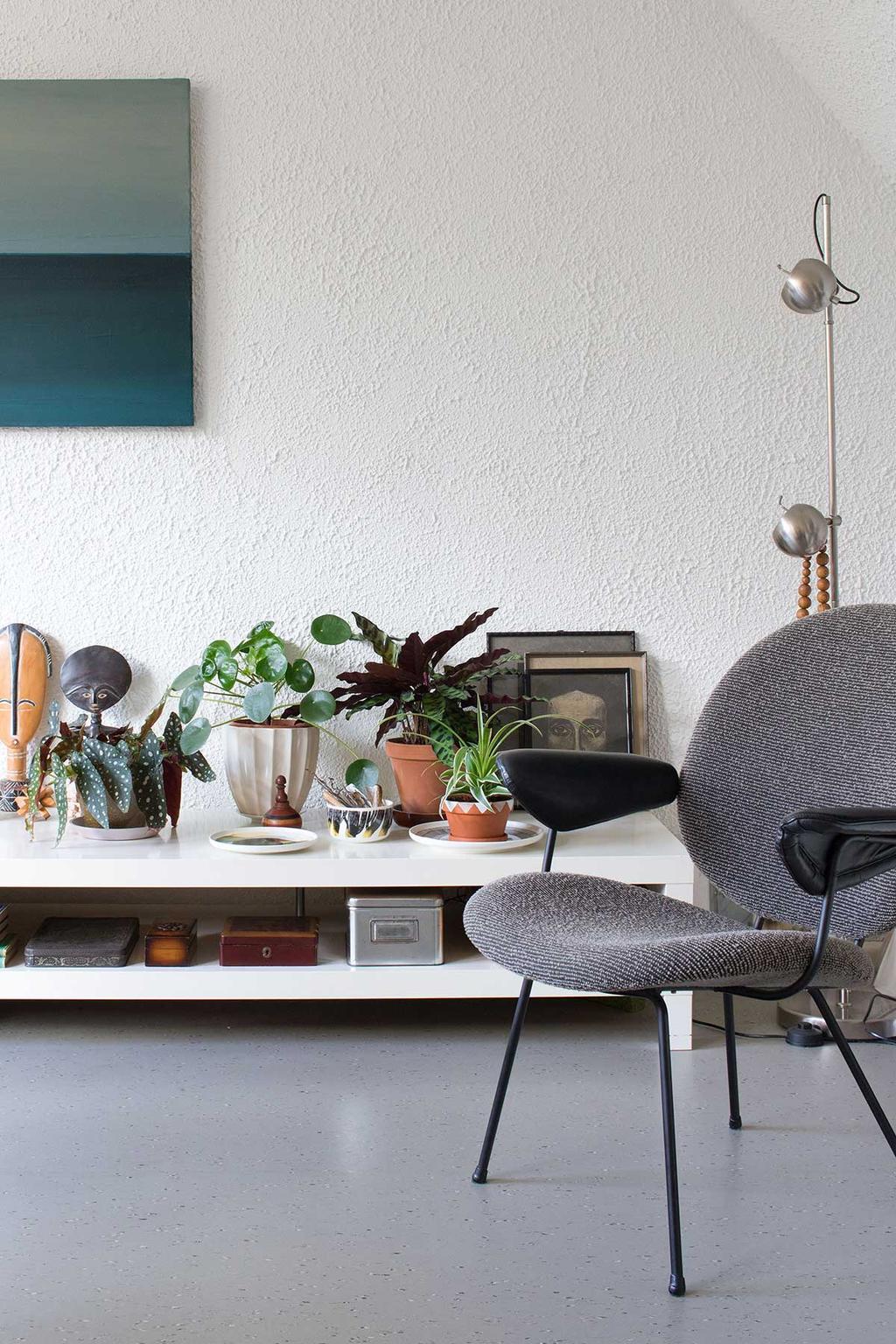 Plantenpodium met grijze stoel.