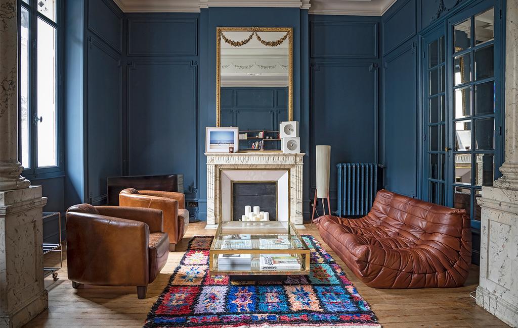 vtwonen special zomerhuizen 07-2021 | blauwe woonkamer met donkere tinten, een bruine bank en fauteuils
