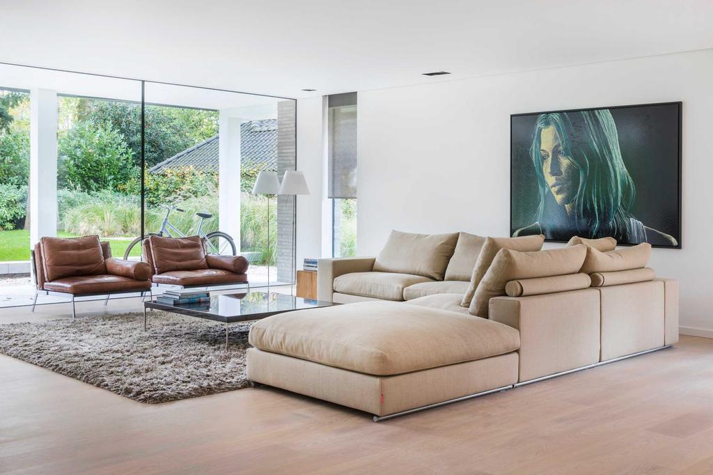 bk 1 woonkamer met beige zetels en planten en een groot schilderij