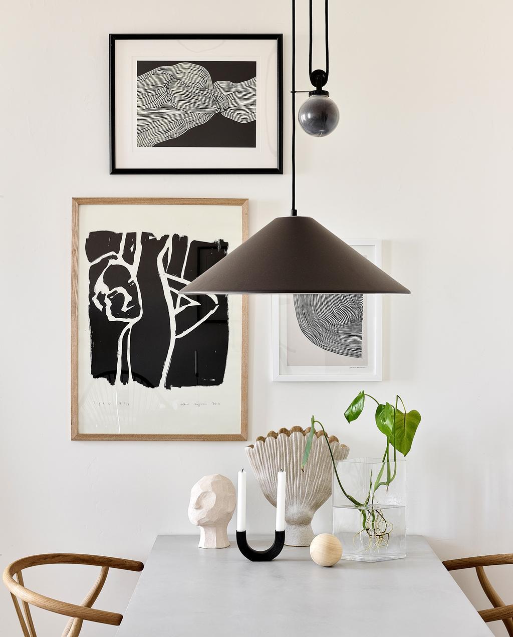 vtwonen special tiny houses | posters aan de muur met een zwarte lamp en lange tafel