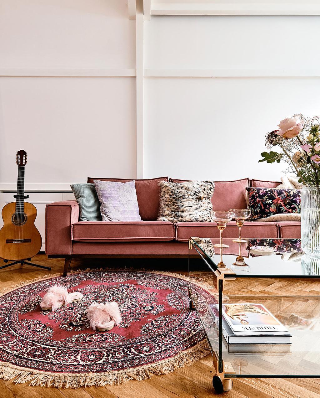 vtwonen 06-2021   rond vloerkleed met rode bank en pantoffels op de vloer, met een gitaar op de achtergrond