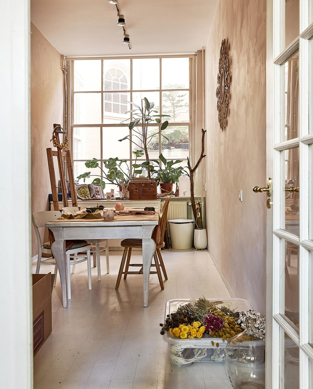 vtwonen 06-2021 | houten tafel in een soort werkkamer met een schildersezel