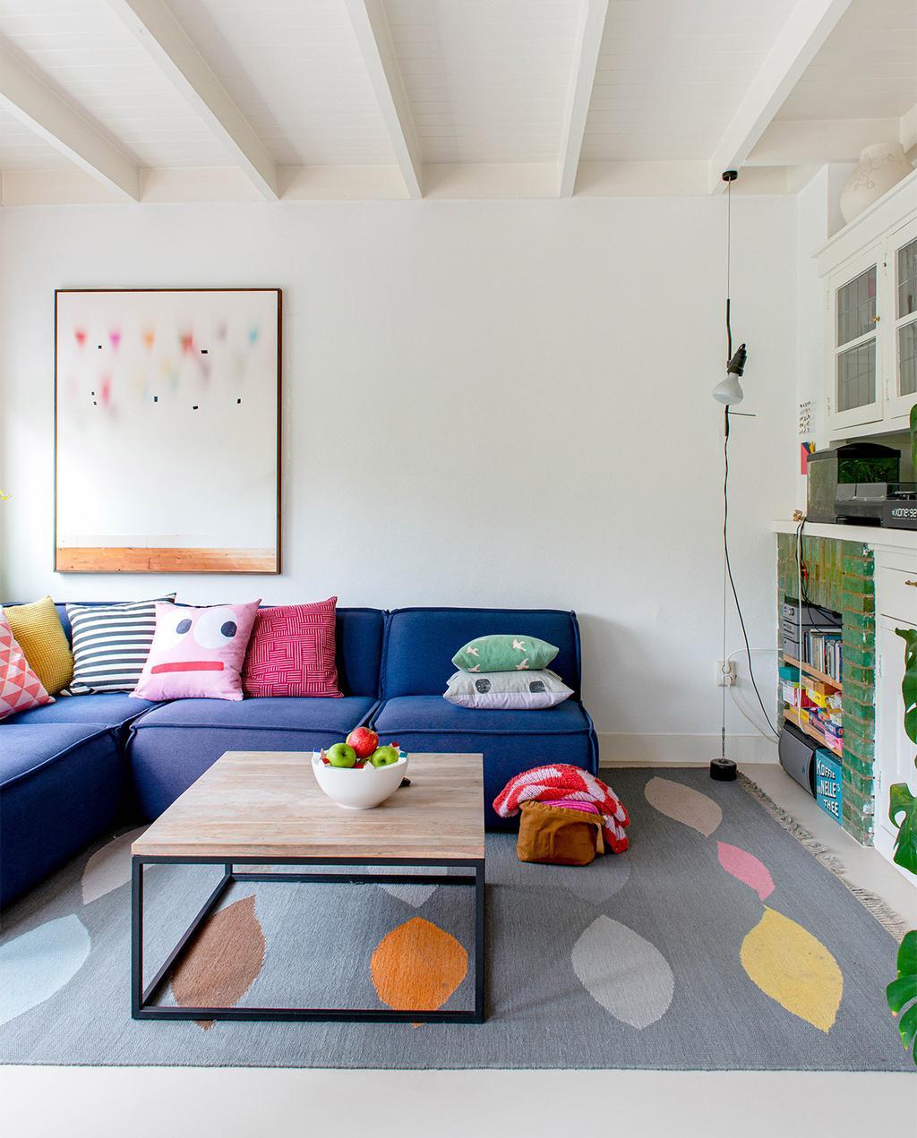 vtwonen 07-2021 | kleurrijk vloerkleed met een gele kattenmand en opvallende kussens