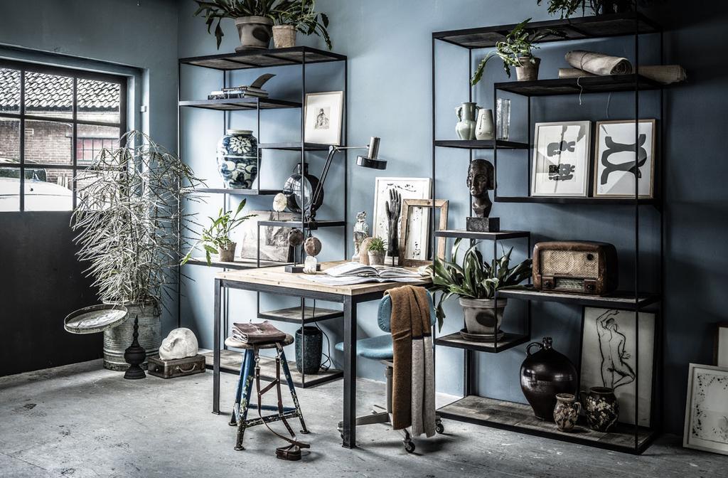 Zwarte stellingkasten met accessoires tegen blauwe muur