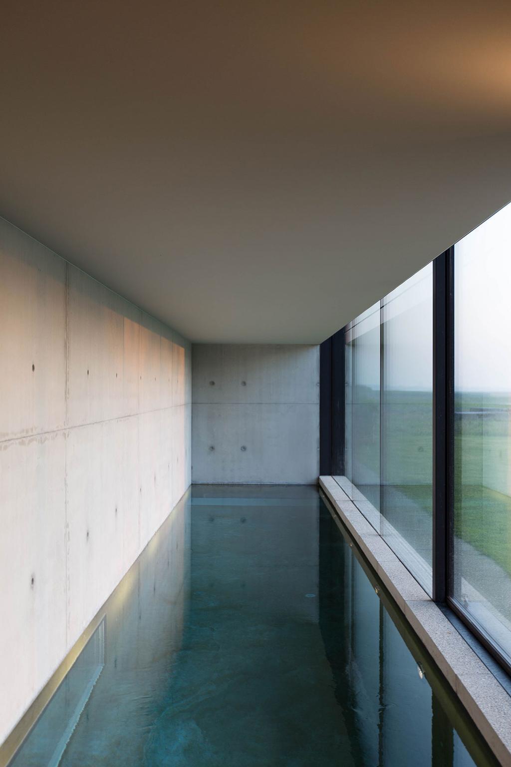 Een lang, smal binnenzwembad omgeven door glas en beton.