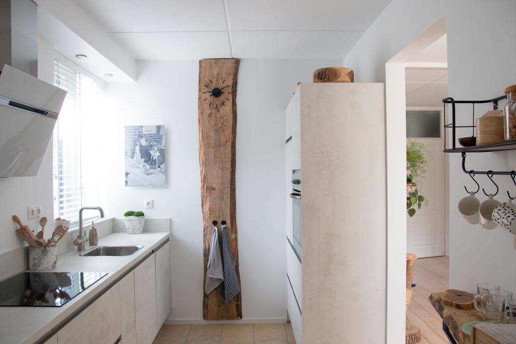 overzicht-van-de-keuken-met-tegen-de-wand-ter-decoratie-een-eikenhouten-boomstamplank