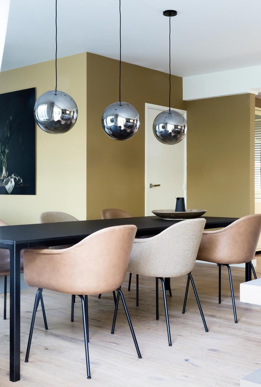 Weer verliefd op je huis: gouden wand bij de eettafel met glazen hanglampen