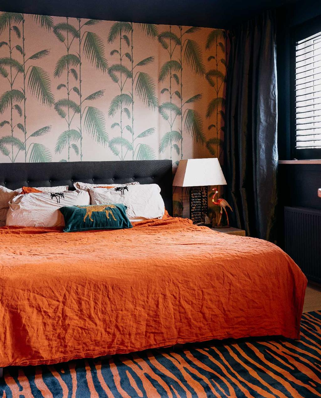 vtwonen 11-2020 | binnenkijken bont familiehuis Amsterdam zwoele slaapkamer met roze palm behang, terra bedsprei en rood tijgerprint vloerkleed