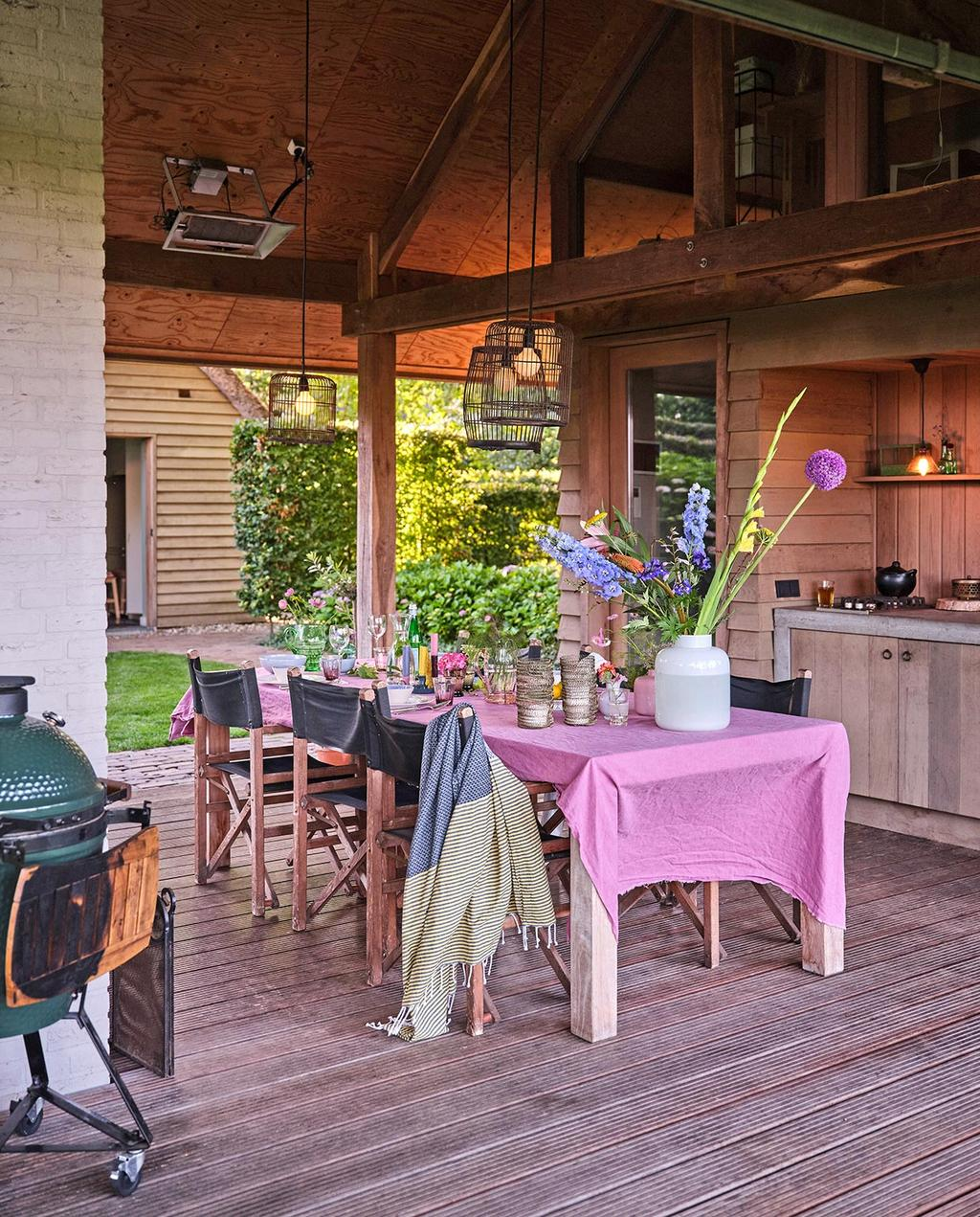 vtwonen tuin 03-2021 | buitentafel in tuinhuis met groene barbecue en roze tafelkleed