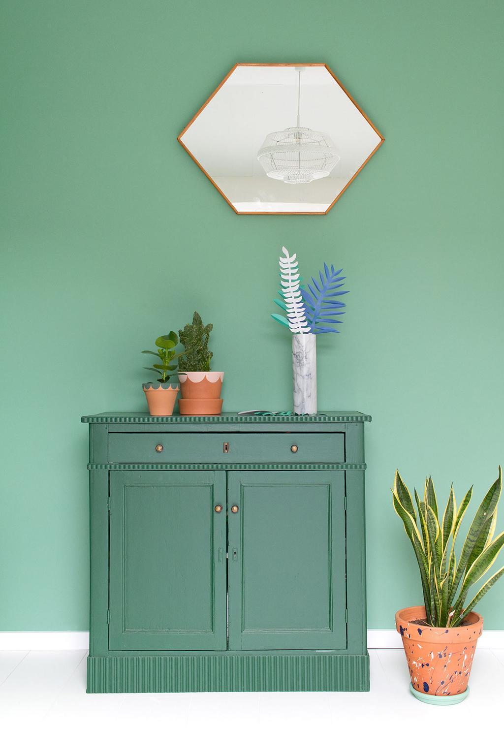 Vaas met bloemen van papier op een groene kast tegen een groene muur