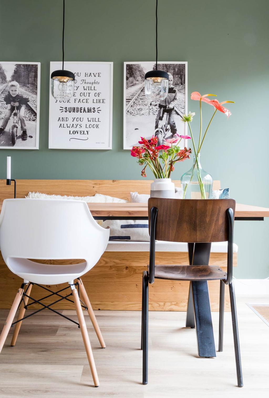 Eettafel met verschillende stoelen tegen groene muur