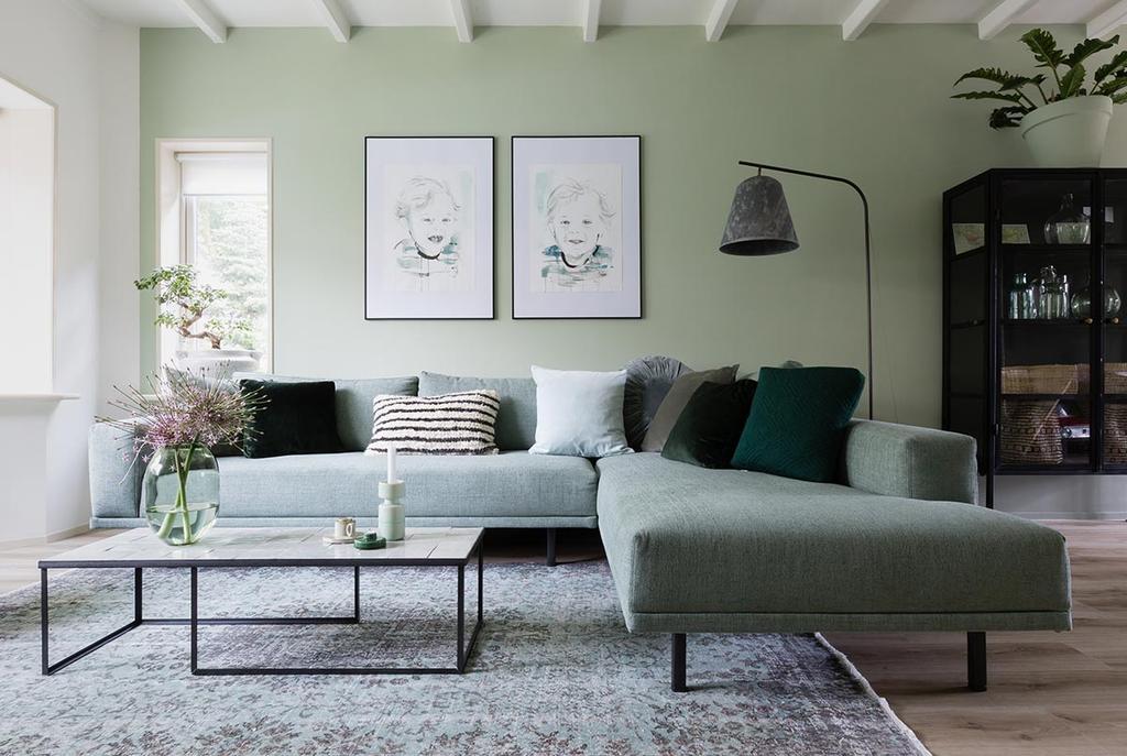 Groene woonkamer met grijze hoekbank en portretschilderijen