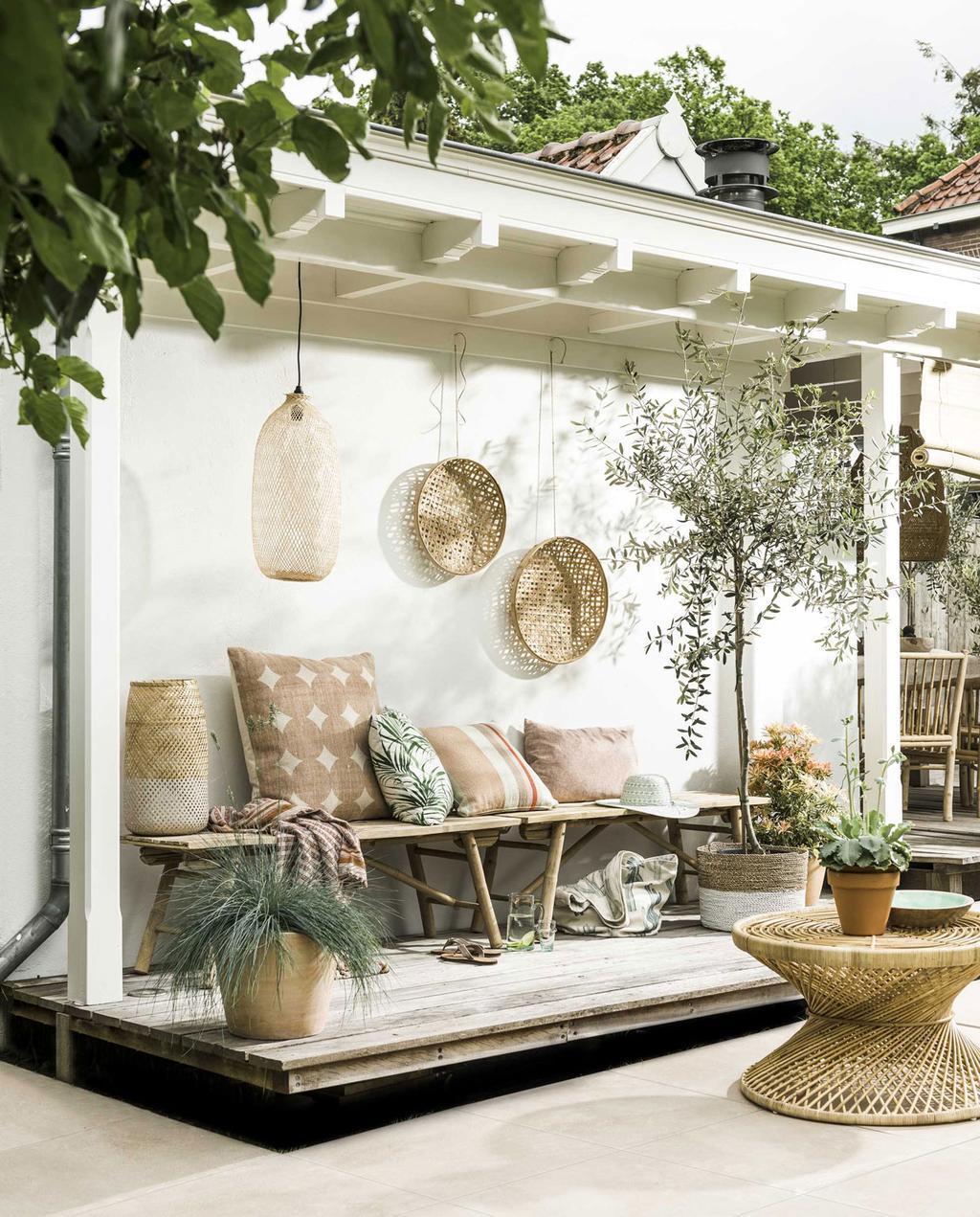 overdekt terras met rieten manden aan de muur en een rieten bijzettafel