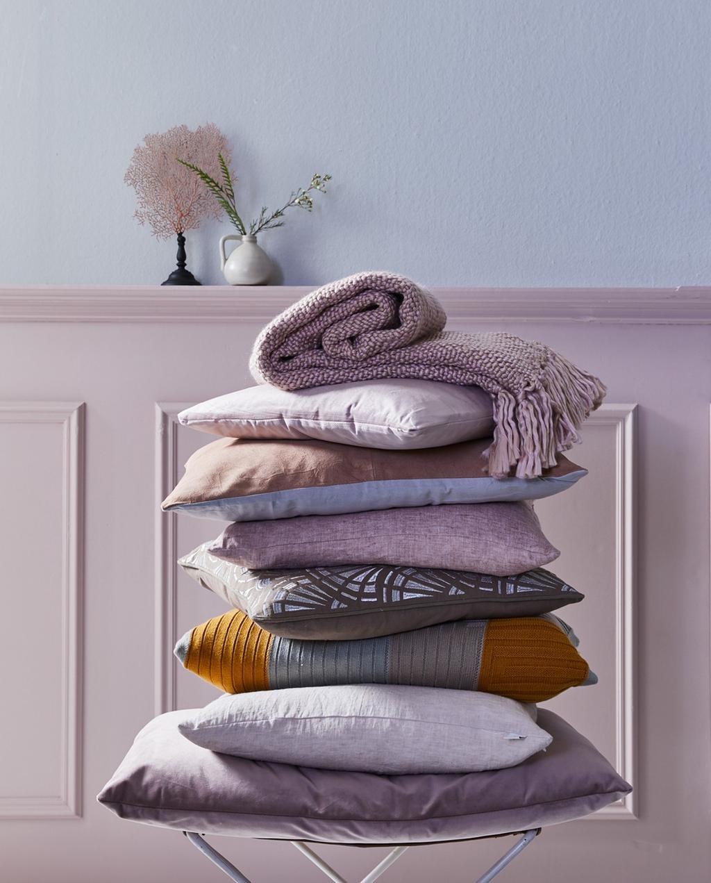 Stapel met roze kussens en knusse items in het vtwonen voorjaarshuis