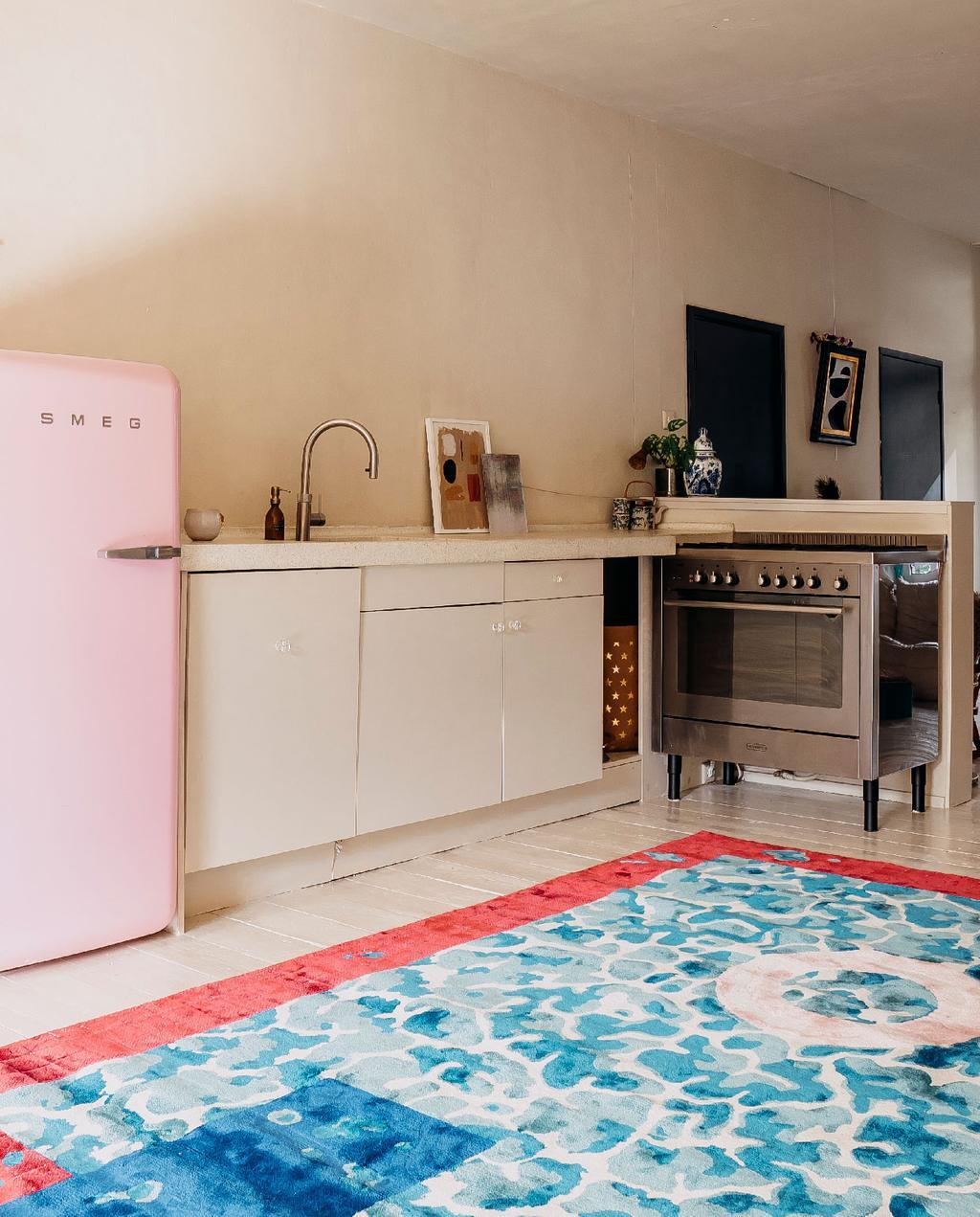 vtwonen 11-2020 | binnenkijken amsterdam open leefkeuken witte keukenkastjes, roze smeg koelkast, groot fornuis en vloerkleed met blauw dessin