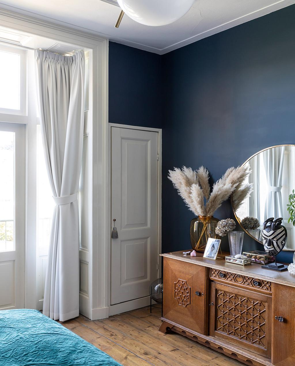 vtwonen 01-2021 | slaapkamer met donkerblauwe muur, kast met pluimen in vaas