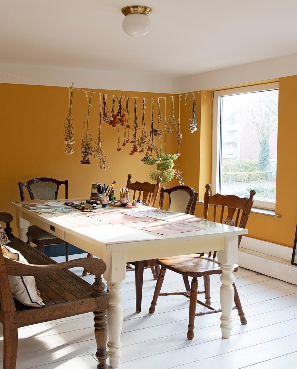 vtwonen 03-2021   eettafel met verschillende vintage stoelen en okergele muur