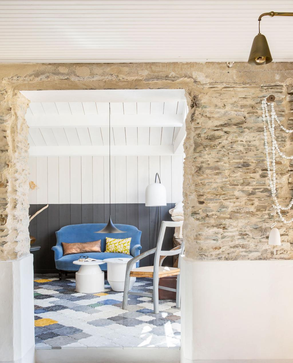 vtwonen binnenkijken special 07-2021 | binnenkijken in een vissershuis | woonkamer met houten wanden en lambrisering van wit en navy, een felblauwe bank en blauw, wit en gele vloertegels
