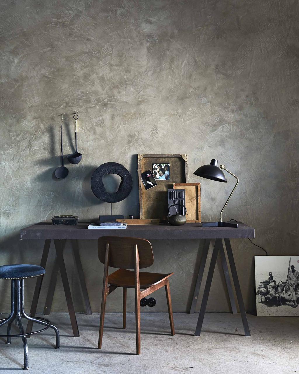 Zwart bureau met donkere decoratie en houten stoel
