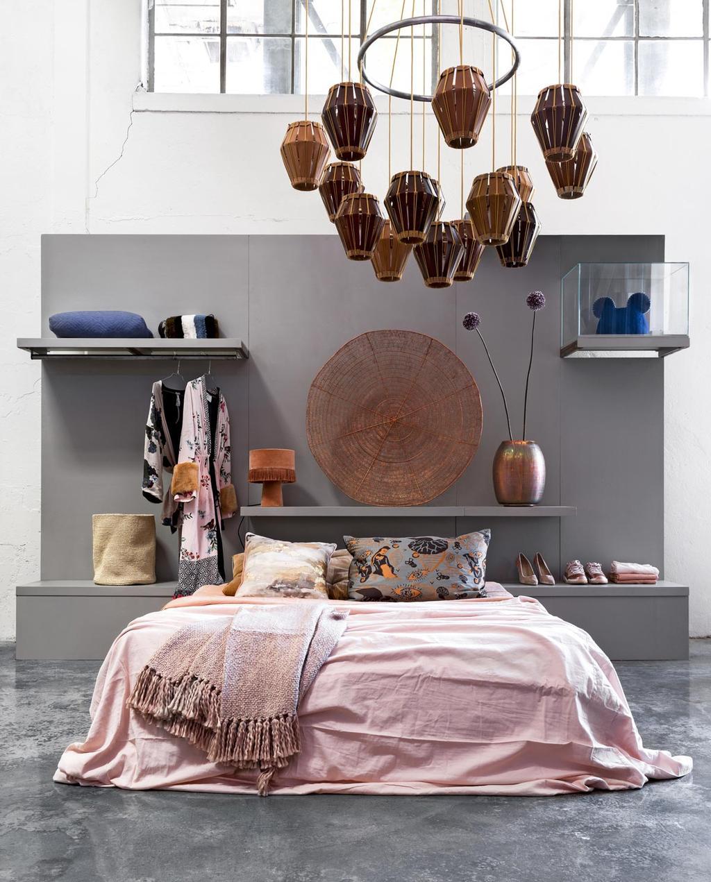 Een slaapkamer met een warm, roze dekbed en koperen accessoires.