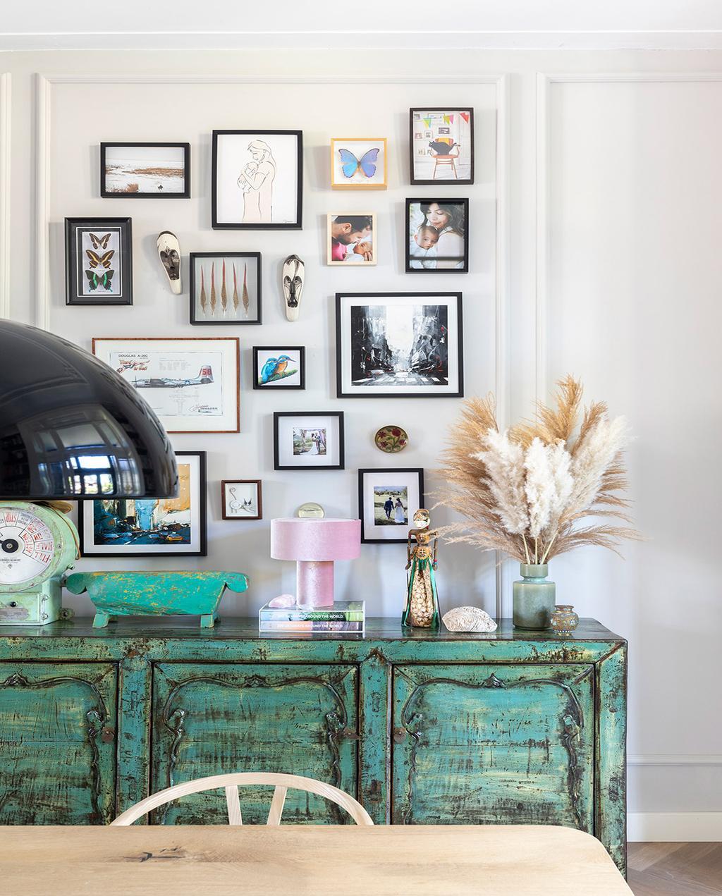 vtwonen 01-2021 | binnenkijken bij interior junkie fotomuur met verschillende lijstjes en groene kast