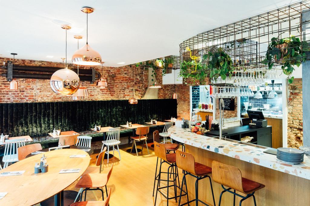 Interieur van Marloo's Hasselt met houten stoelen en barkrukken en terrazzo afwerking aan de bar