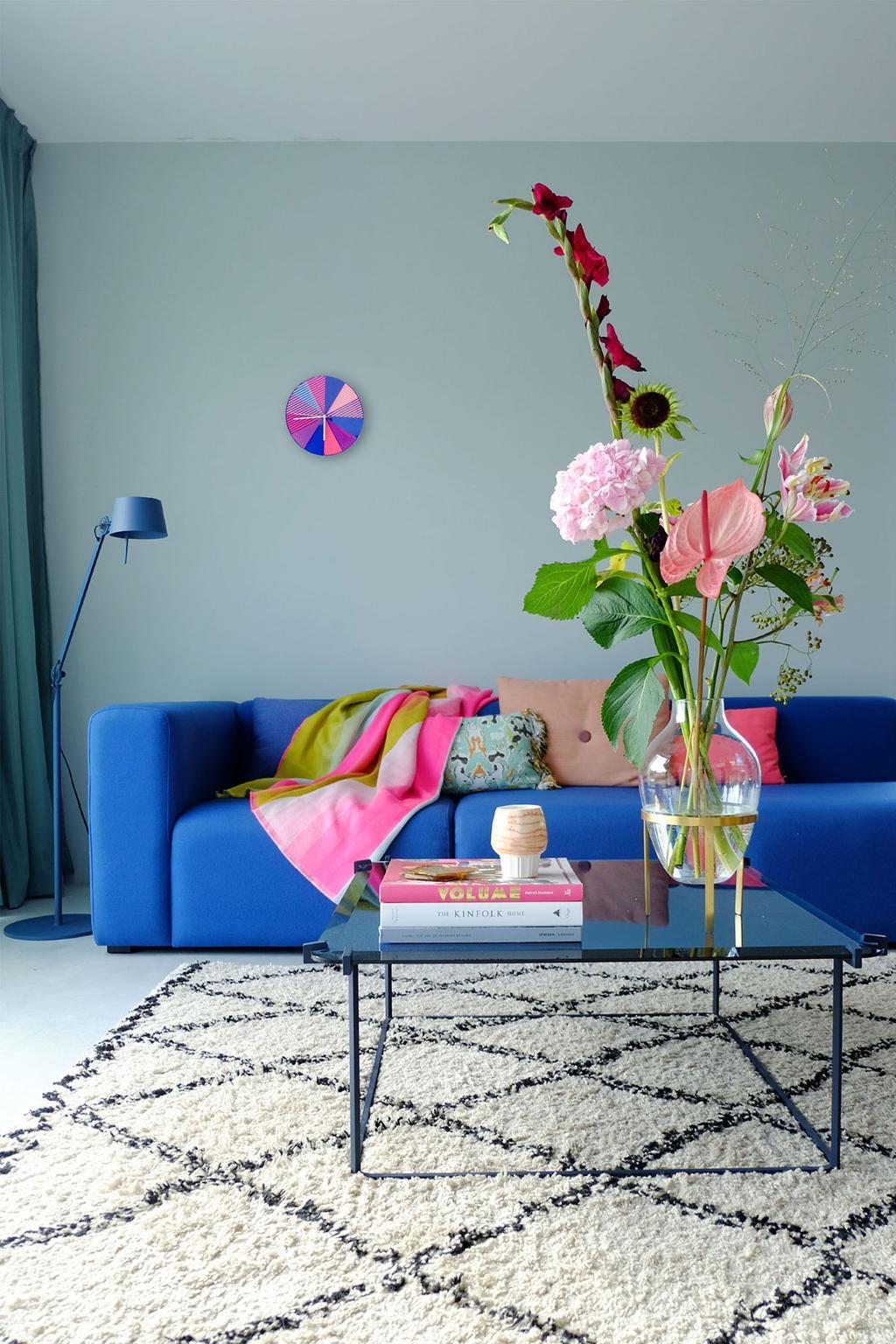Blauwe bank van HAY, salontafel van Linteloo en een geruit vloerkleed in de woonkamer van PRCHTG