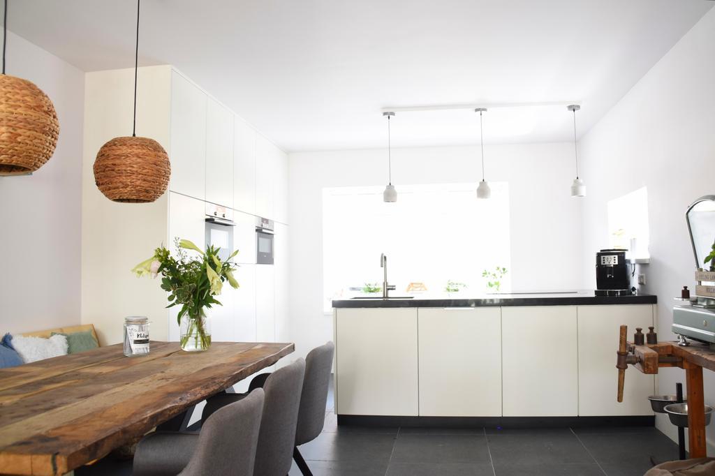 een-strakke-keuken-gecombineerd-met-robuuste-landelijk-meubels-samen-een-gezellige-woonkeuken-het-kookeiland-van-maar-liefst-is-1-35-x-240-meter-heeft-een-geintegreerde-afzuigkap-zodat-er-plek-is-voor-leuke-kleine-hanglampjes-boven-het-aanrecht