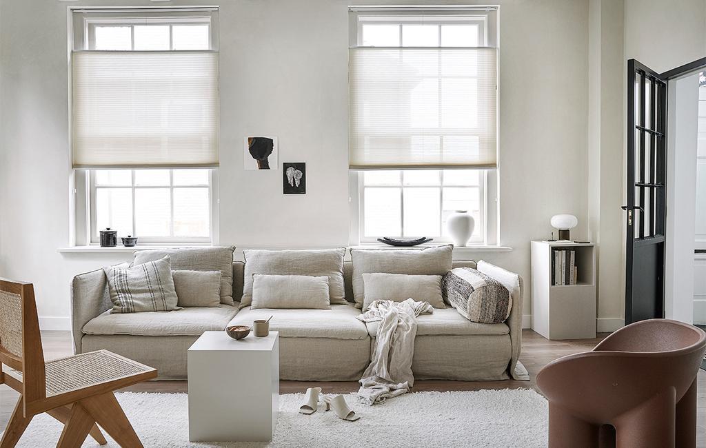 vtwonen 09-2021 | Lichtdoorlatend plisségordijn lichte bank met vloerkleed en rotan fauteuil